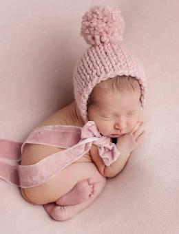 Knitted bonnet with pom pom and pants for baby girl photo shoot